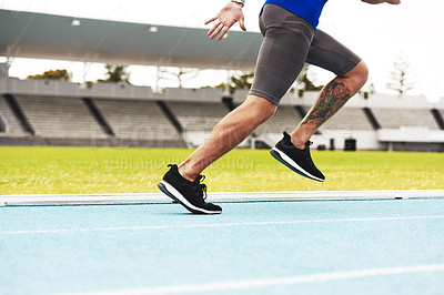 Buy stock photo Cropped shot of an unrecognizable young male athlete running along the track