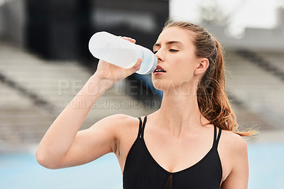 Buy stock photo Cropped shot of an attractive young female athlete drinking water while out on the track