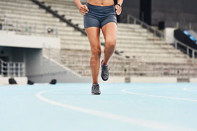 Buy stock photo Cropped shot of an unrecognizable young female athlete running along the track