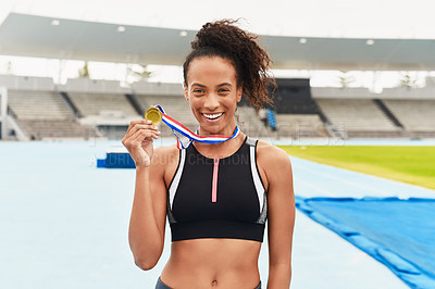 Buy stock photo Cropped portrait of an attractive young female athlete posing with her gold medal out on the track