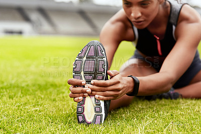 Buy stock photo Cropped shot of an attractive young female athlete warming up at the track