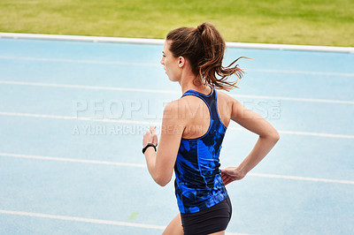 Buy stock photo Rearview shot of an attractive young woman running along the track