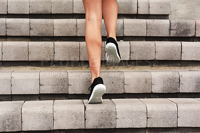 Buy stock photo Rearview shot of an unrecognizable young female athlete working out on a flight of stairs at the track