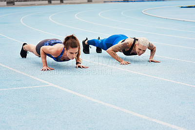 Buy stock photo Full length shot of two attractive young female athletes doing pushups out on the track