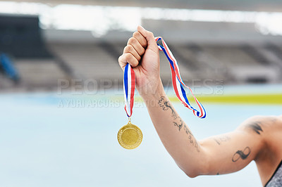 Buy stock photo Cropped shot of an unrecognizable young woman posing with her gold medal out on the track
