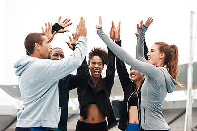 Buy stock photo Cropped shot of a diverse group of athletes standing and giving each other a high five after a track session