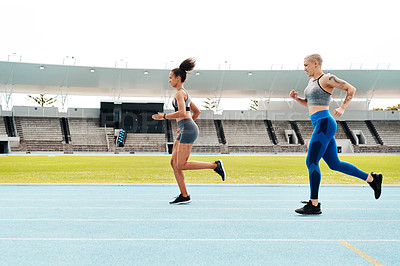 Buy stock photo Full length shot of two attractive young athletes running a track field together during an outdoor workout session