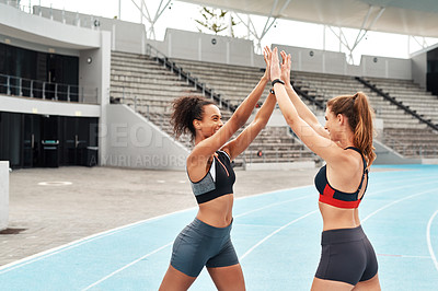 Buy stock photo Cropped shot of two attractive young athletes standing together and giving each other a high five after running