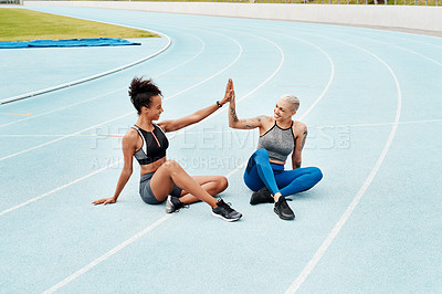 Buy stock photo Full length shot of two attractive young athletes sitting together and giving each other a high five after running