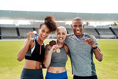 Buy stock photo Cropped portrait of a diverse group of athletes standing together and holding up medals after winning a running race