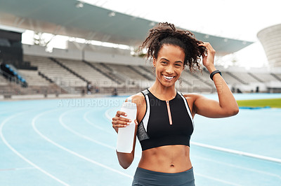 Buy stock photo Cropped portrait of an attractive young athlete standing alone and holding a bottle of water during an outdoor training session