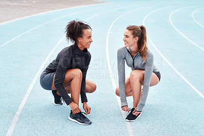 Buy stock photo Full length shot of two attractive young athletes crouching together and tying their shoelaces before running on a track