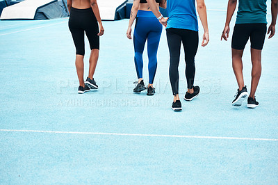 Buy stock photo Cropped shot of an unrecognizable group of athletes walking together after a running race on a track field