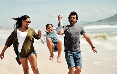 Buy stock photo Shot of an adorable little girl having a fun day at the beach with her parents