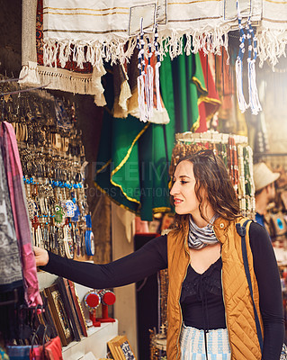 Buy stock photo Shot of a young woman shopping for fabric at a local market stall