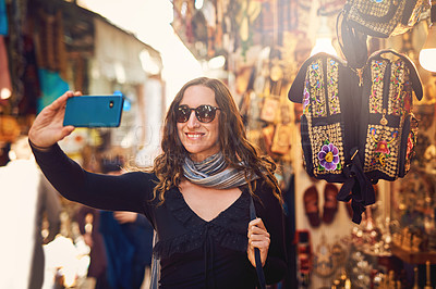 Buy stock photo Shot of a young woman taking a selfie while exploring a marketplace in Israel