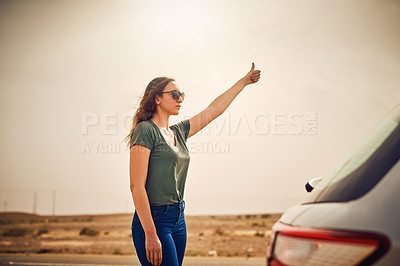Buy stock photo Shot of a young woman hitchhiking on a country road after breaking down