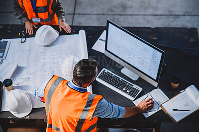 Buy stock photo High angle shot of two engineers working together on blueprints while making use of a computer inside of a workshop
