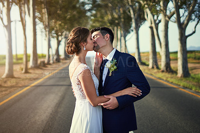 Buy stock photo Shot of a happy young couple standing on a country road and kissing on their wedding day