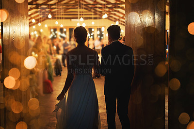 Buy stock photo Rearview shot of a young couple arriving hand in hand at their wedding reception