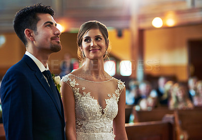 Buy stock photo Shot of a young bride looking fondly at her groom during the wedding ceremony