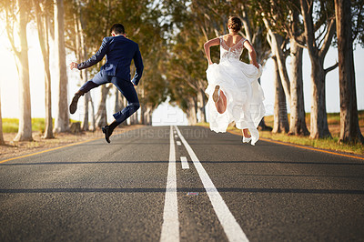 Buy stock photo Rearview shot of a young couple jumping for joy on a country road on their wedding day