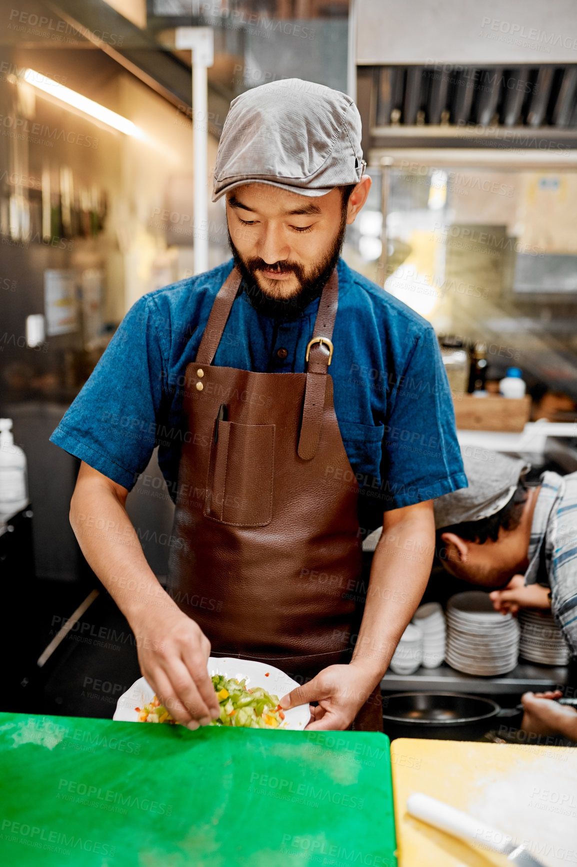 Buy stock photo Shot of a handsome young chef preparing a meal inside the kitchen of a cafe