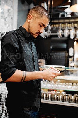 Buy stock photo Shot of a handsome young businessman using a cellphone inside his cafe