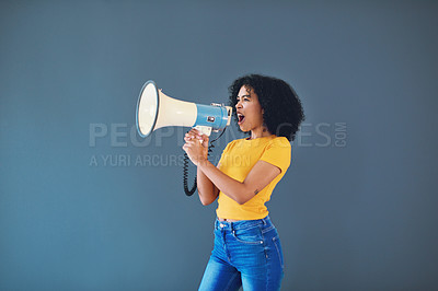 Buy stock photo Cropped shot of an attractive young woman using a megaphone while standing against a grey background