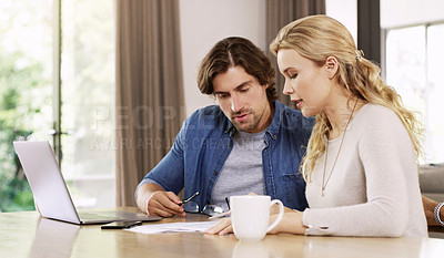Buy stock photo Shot of a young couple going over finances and paperwork together at home