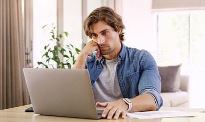 Buy stock photo Shot of handsome young businessman looking stressed out while working on his laptop at home