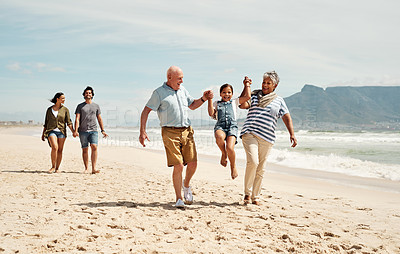 Buy stock photo Shot of an adorable little girl having a fun day at the beach with her parents and grandparents