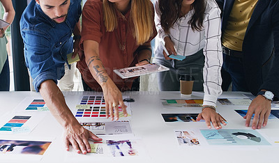 Buy stock photo Closeup shot of a group of designers going through paperwork together in an office