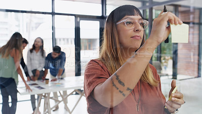 Buy stock photo Shot of a young businesswoman brainstorming with notes on a glass wall in an office