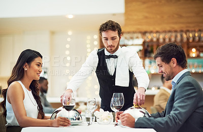 Buy stock photo Cropped shot of a handsome young waiter serving a young couple in a restaurant