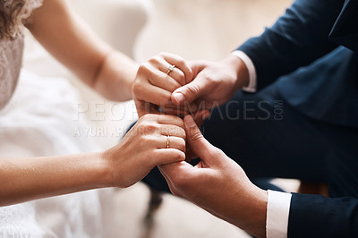 Buy stock photo Cropped shot of an unrecognizable newlywed couple affectionately holding hands after their wedding