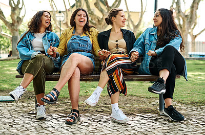 Buy stock photo Full length shot of a young group of students sitting cross legged on a park bench after a study session