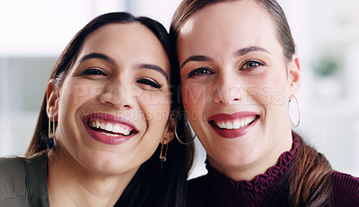 Buy stock photo Cropped portrait of two attractive young businesswomen smiling and standing together in the office during the day