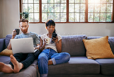 Buy stock photo Shot of a young couple using a laptop while relaxing on the sofa at home
