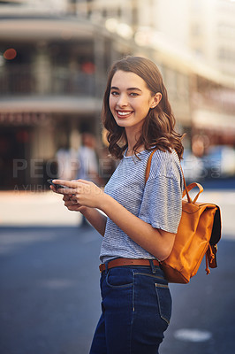 Buy stock photo Cropped portrait of an attractive young woman sending text messages while spending her day out in the city