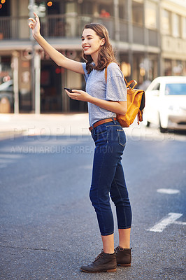 Buy stock photo Full length shot of an attractive young woman sending a text message while hailing a taxi out in the city