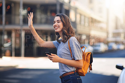 Buy stock photo Cropped shot of an attractive young woman sending a text message while hailing a taxi out in the city