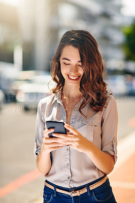 Buy stock photo Cropped shot of an attractive young businesswoman sending text messages during her morning commute to work