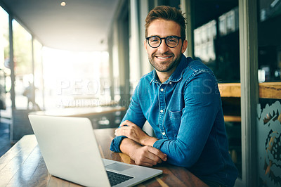 Buy stock photo Cropped portrait of a handsome young businessman sitting alone and working in a cafe during the day