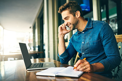 Buy stock photo Cropped shot of a handsome young businessman sitting alone and talking on his cellphone while using his laptop