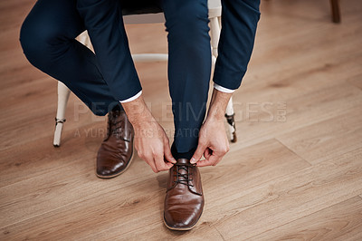 Buy stock photo Cropped shot of an unrecognizable bridegroom tying his shoelaces in preparation for his wedding