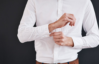 Buy stock photo Cropped shot of an unrecognizable bridegroom adjusting his shirt's button in preparation for his wedding