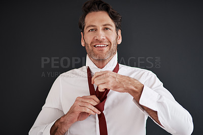 Buy stock photo Cropped shot of an attractive middle aged bridegroom adjusting his necktie in preparation for his wedding