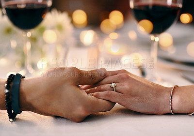 Buy stock photo Cropped shot of an unrecognizable couple holding hands while sitting in a restaurant