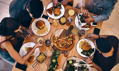 Buy stock photo High angle shot of a group of friends eating out